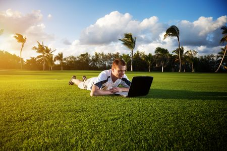 young man whith notebook on the green field and sunset Stock Photo - 5999056