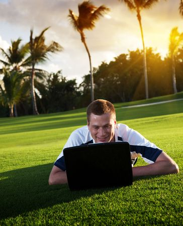 young man whith notebook on the green field and sunset Stock Photo - 5999054
