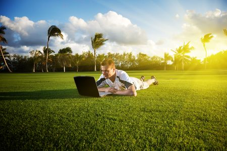 young man whith notebook on the green field and sunset Stock Photo - 6059816