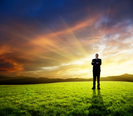 successful leadership: young businessman on green field and sunset