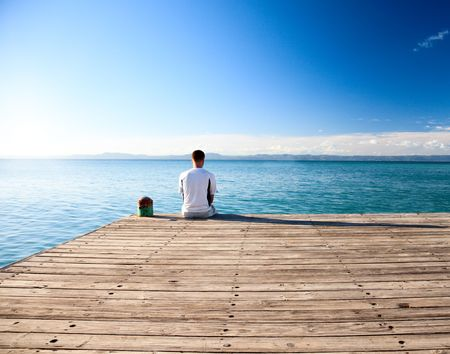 lonely boy: young man relax siting on pier