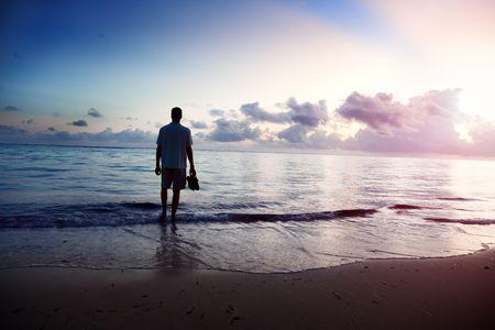 person walking: young man and sunset on sea Stock Photo
