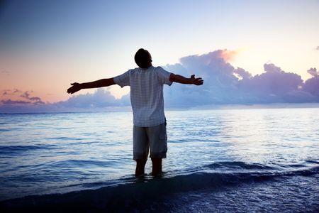 바다와 일출에 행복한 젊은이
