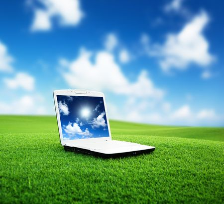 green computing: notebook on the green field of spring grass