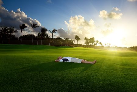 farm boys: young man relax on green grass in sunset time Stock Photo