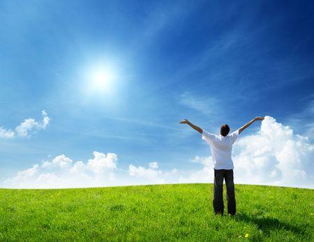 gebied van gras en gelukkige jonge man  Stockfoto