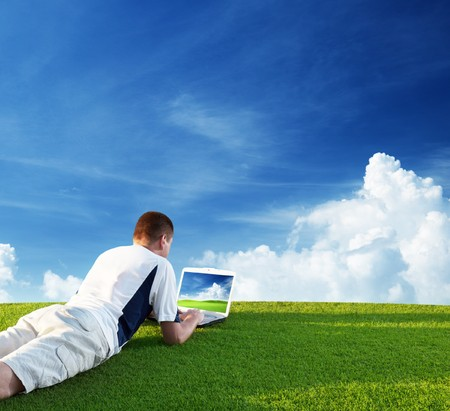 Young man use a notebook on green field Stock Photo - 7578725