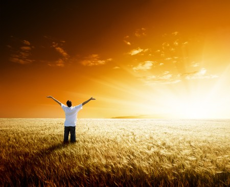 sunrise field: happy young man rest on wheat field