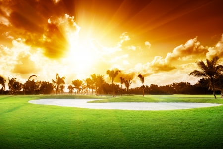 playing golf: sunset on golf field