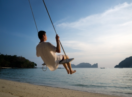 Phi: young man on beach swing Phi Phi Thailand