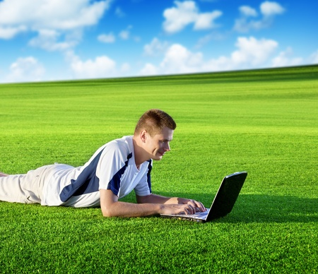 Young man use a notebook on green field photo