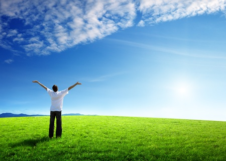 freedom concept: happy young man on green field