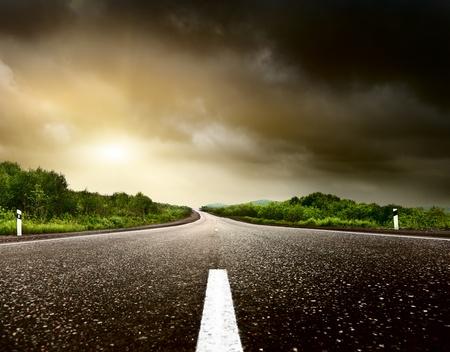 carretera: cielo tormentoso y el camino en el bosque