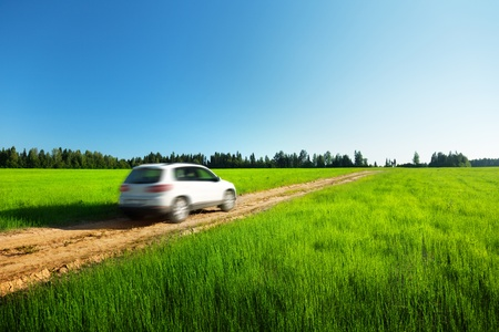 off road vehicle: spring field and blured car on ground road