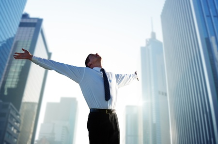 victory: happy young businessman and big city
