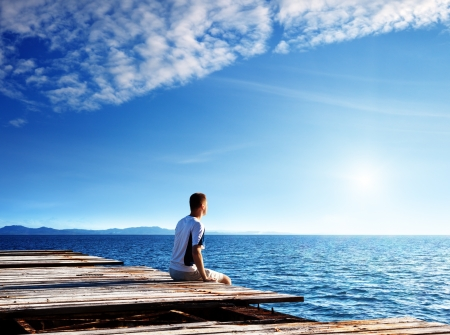young man relax siting on pier  photo
