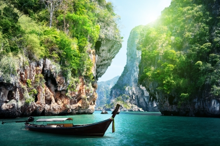 long boat and rocks on railay beach in Krabi, Thailand photo