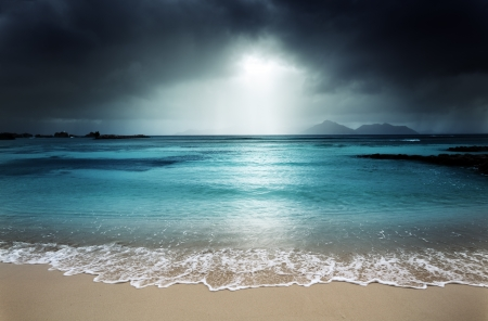 natural disaster: dark sky on the beach of la Digue island, Seychelles Stock Photo