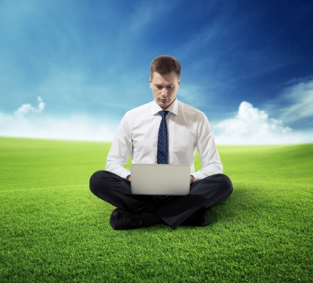 business man with notebook sitting on grass photo