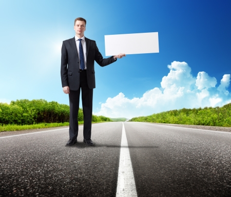 business man on the road with blank in hand Stock Photo - 18765622
