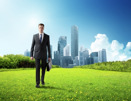 business man walking on green field and modern city photo