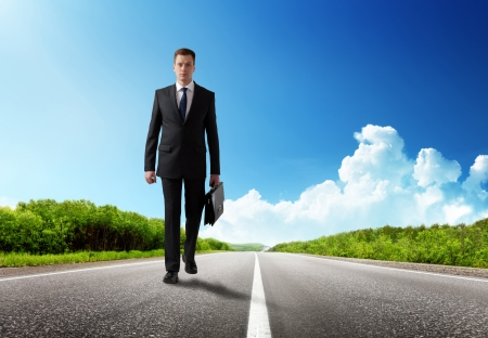 business trip: business man walking on the road Stock Photo