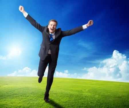 hombres corriendo: Hombre de negocios feliz que se ejecuta en campo de primavera Foto de archivo