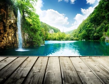 Wodospad w głębokim lesie w Chorwacji i drewniane molo