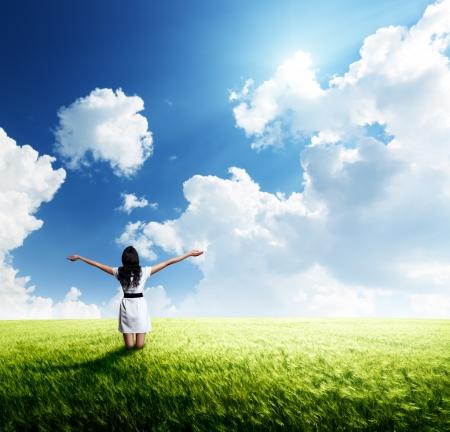 glädje: lycklig ung kvinna i vit klänning stående i fält Stockfoto