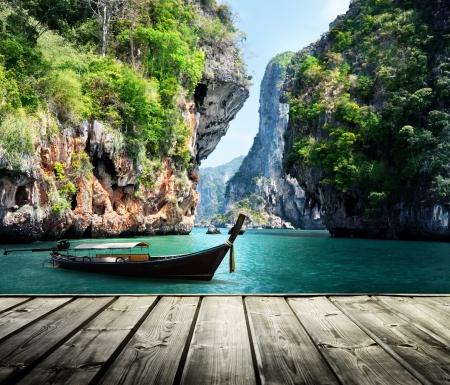 tabla de surf: barco largo y rocas en playa Railay en Krabi, Tailandia