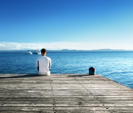 wooden dock: young man relax siting on pier