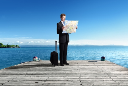 Business man standing on pier with map in hands photo