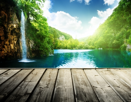 waterfall in deep forest of croatia and wood pier photo