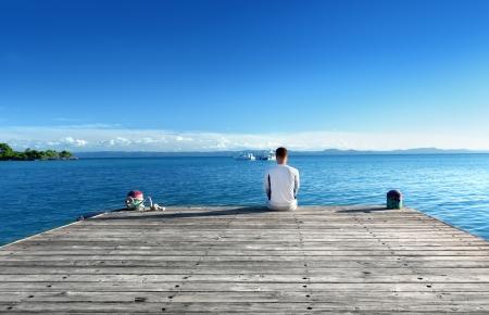 若い男リラックス桟橋に立地