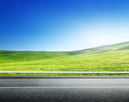 asfaltweg en perfecte groene veld Stockfoto