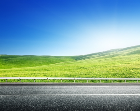 road ahead: asphalt road and perfect green field