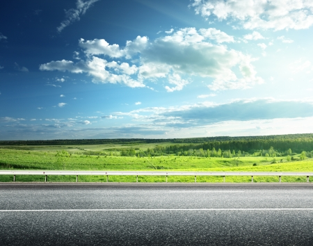 side views: asphalt road and perfect green field