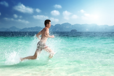 running man in water of tropical sea photo