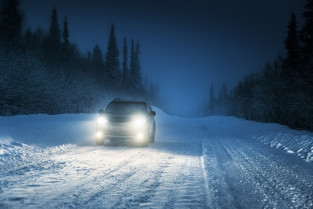 Car lights in winter Russian forest photo