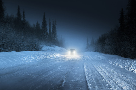 dark: Car lights in winter Russian forest