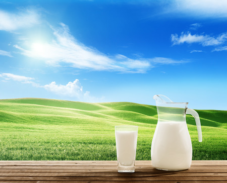 milk jugs: milk and sunny spring field Stock Photo