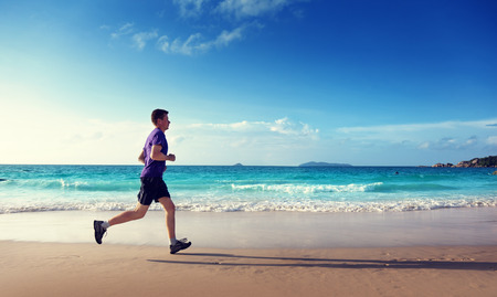 Man running on tropical beach at sunset photo