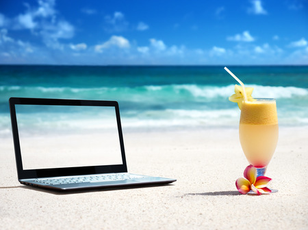 notebook on the beach and glass of fresh jucie Stock Photo - 25908984