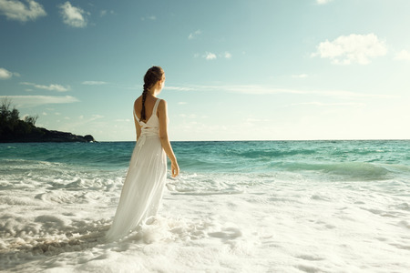 young woman standing in sea waves  photo