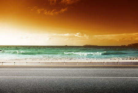 gold road: road and sea in sunset time Stock Photo