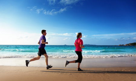 Man and women running on tropical beach at sunset  photo