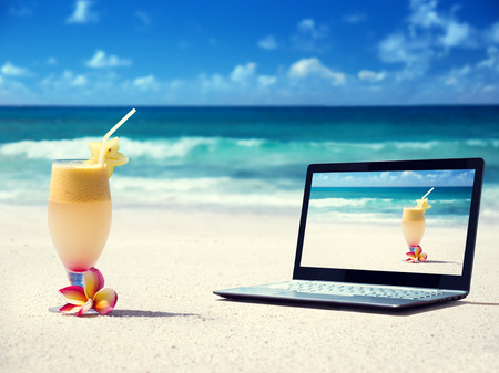 notebook on the beach and glass of fresh jucie Banco de Imagens