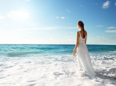 white dresses: young woman standing in sea waves  Stock Photo
