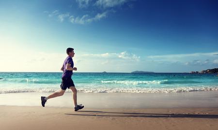 hombres corriendo: Hombre que se ejecuta en la playa tropical al atardecer