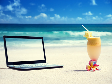 notebook on the beach and glass of fresh juice photo